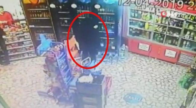 Çaldığı içki şişesini montuna saklayan hırsız kamerada